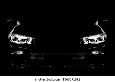 Black modern car headlights - front view. Silhouette of black sports car with headlights on black background.