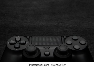 Black modern gamepad on a dark wooden background