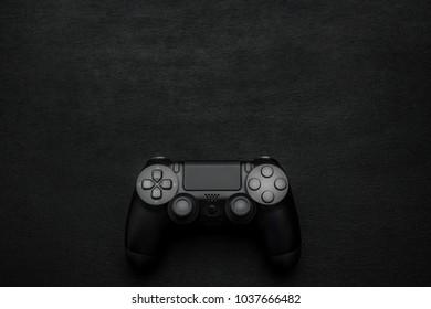 Black modern gamepad on a dark wooden background