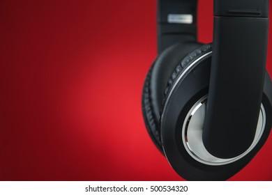 Black modern headphones on red background