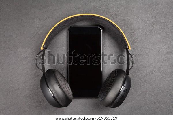Black modern smartphone and headphones