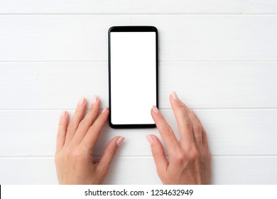 Black modern smartphone with white screen in hands on white table background