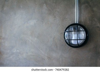 Black modern vintage style wall light with metal wire pipe (EMT pipe) on concrete loft style wall. Copy space. Concept for interior design and architecture.
