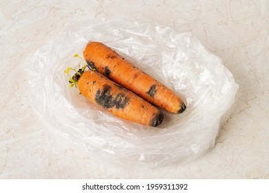 Black mold stains on two raw carrots in a plastic bag on a kitchen table. Fungal mold on rotten carrots. Spoiled fruits and vegetables. Food forgotten in the fridge. Biodegradable food waste. Close-up