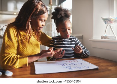 Black mom and child doing homework at kitchen
