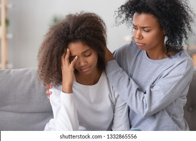 Black mom kid sitting on couch, mother calms frustrated daughter, older sister make peace after quarrelling with younger relative person. Teen problems, emotional disorders first unhappy love concept