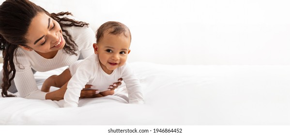 Black Mom Posing With Baby Toddler Holding Helping Her Son Crawl On White Studio Background. Happy Young Mother Caring For Child Infant Bonding And Playing With Cute Little Boy. Panorama, Copy Space