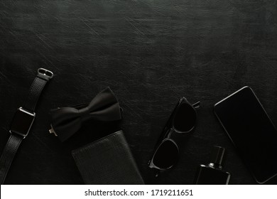 Black monochromatic composition on black background: watch, phone, sunglasses, purse, perfume, male butterfly. Minimalist black. Mens accessories. Copy space.