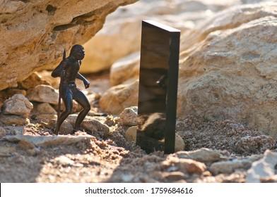 Black monolith on old sandstone rock near the sea coast and Cro-Magnon man with spear