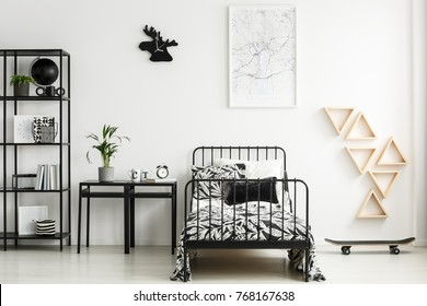 Black moose shaped clock hanging on white wall in teenager's bedroom with metal furniture and map poster