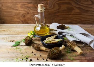 Black morel mushrooms in skillet on rustic wooden background. Healthy eating vegetarian food.