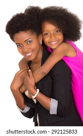 Black mother daughter posing happily with girl hanging over moms shoulder closeup