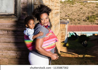 Black mother and duaghter  standing in the township