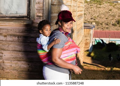 Black mother with her daughter on her back while they are in the township