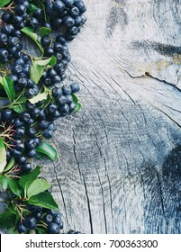 Black mountain ash against a textural old wooden surface (Aronia melanocarpa). Autumn background.