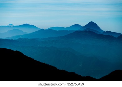 Black Mountain Silhouette in front of Skyscape cold blue mountains with mist and fog close to Quetzaltenango in Guatemala