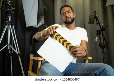 Black movie director sitting in a director's chair