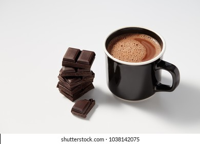 Black mug with hot chocolate served with chunks of dark chocolate