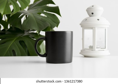 Black mug mockup with a candle holder on a white table and a monstera plant.