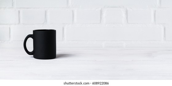 Black mug on white table against white brick wall background. Closeup. Copy space.