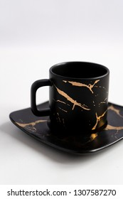 Black mugs with a saucer. Cups for coffee and tea on a white background. Utensils for any holiday, luxury wedding, birthday or party. Style Japanese art of repair broken dishes, kintsugi. Gold streaks