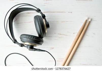 Black music headphones with drum sticks on wooden background