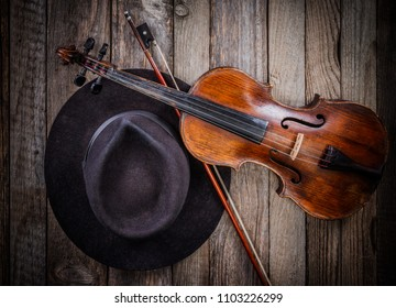 Black musician hat and violin on wooden table