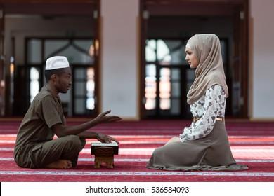 Black Muslim man and woman praying in mosque