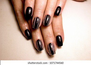 Black nail polish. Manicured nail with black nail polish. Manicure with dark nailpolish. Black nail art manicure