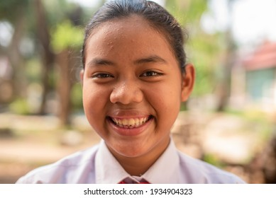 A black native Asian teenage girl in a white high school uniform who had pimple on her forehead  is smiling happily on a hot summer day that makes her sweat on a natural background.