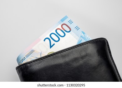 Black natural leather wallet isolated on white background. Expensive man's purse closeup. New russian ruble banknote, Two thousand rubles.
