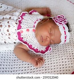 Black newborn baby in white knitted dress and headband sleeping