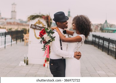 Black newlyweds happily hugging on the rooftop while wedding ceremony