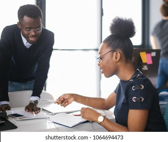black nice students in glasses are studing in the college. male tutor is helping to female who has problems in maths