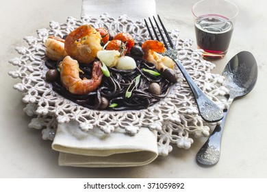 Black noodles with shrimp , garlic , tomatoes and olives