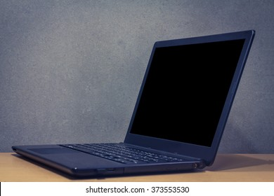 black notebook computer open on gray background wood table