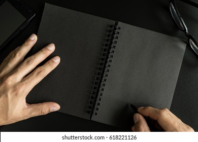 Black notebook with copy space with hand writing on desk office, Top view