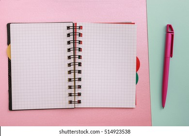 Black notebook lying on a pink background. Pink pen lying on lime background. Management of the day. Education.
