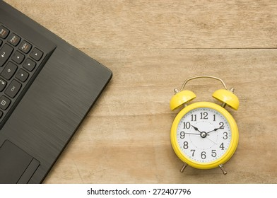 Black notebook  and yellow clock on wooden background.