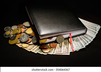 black notepad is on money, dollars, coins inside and near notepad, black background, studio