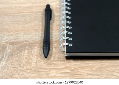 Black notepad and black pen on a wooden table