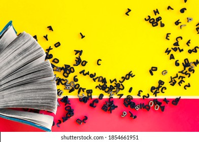 Black numbers and letters of the Latin alphabet chaotically poured out of the pages of an open book onto a yellow-pink paper background. Background from alphabet concept of knowledge and science.
