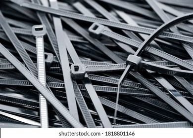 Black Nylon cable ties, hose tie or zip tie background. Flexible nylon tape with an integrated gear rack use for tie and bound cable together