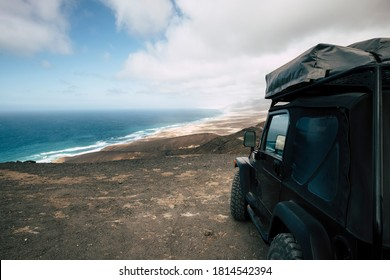 Black off road car parked on the top of a valley with amazing view on a wild beach with nobody - off grid roof tent and adventure lifestyle travel concept