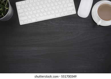 Black office desk table with computer, flower and coffee cup, Top view with copy space