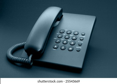 Black office phone with cord isolated on black background