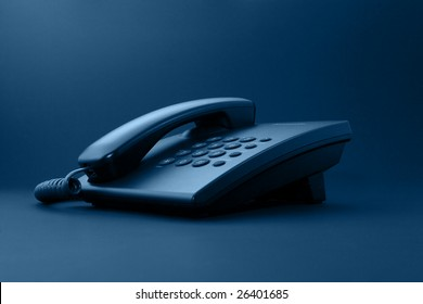 Black office phone with cord isolated on black under sepia