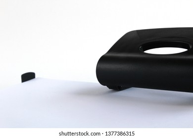 Black office puncher isolated on white background. Shit of paper in hole puncher.