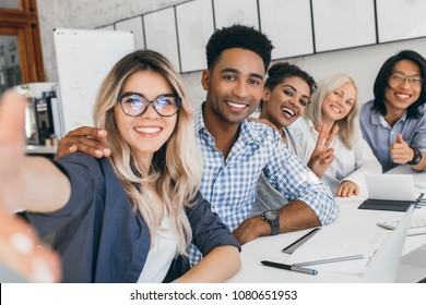 Black office worker in checkered shirt embracing blonde secretary girl while she making selfie. Young managers of international company having fun during meeting.