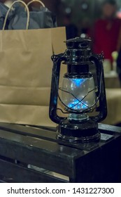 Black, old, 1800s Kerosene lamp decoratign a store, close-up, next to a paper bag with wrapped presents in it, side view